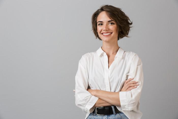 Junge Frau, die die Arme verschränkt und lächelt. © Drobot Dean/stock.adobe.com