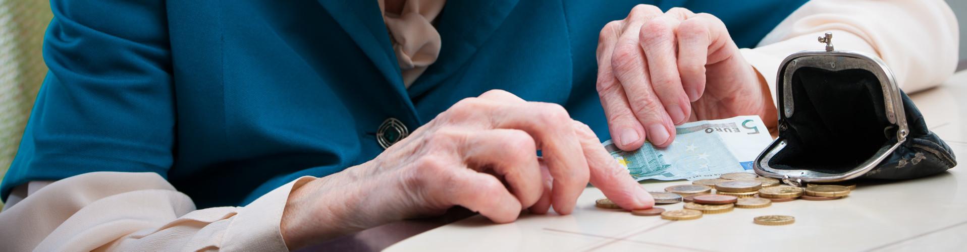 Man sieht die Hände einer älteren Frau, die Kleingeld aus einer Geldbörse zählt © Alexander Raths, stock.adobe.com