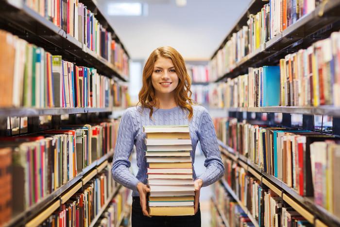 Frau trägt einen Stapel Bücher in einer Bibliothek © Syda Productions/stock.adobe.com