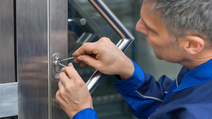 Schlüsseldienstmitarbeiter versucht Türschloss zu öffnen © Andrey Popov/stock.adobe.com