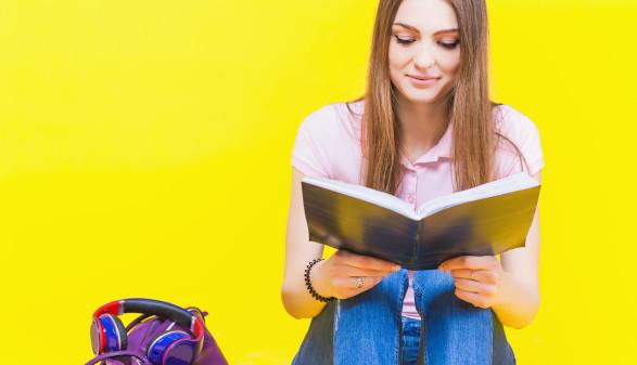 unge Frau mit Schulbuch am Knie © F_Petunyia/stock.adobe.com