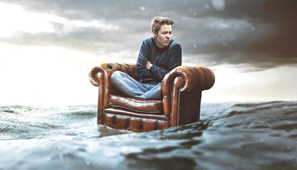 Mann auf Sessel treibt im Meer © lassedesignen/adobe.stock.com