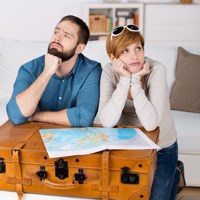 Ein Paar sitzt verärgert mit dem Koffer im Wohnzimmer © contrastwerkstatt/stock.adobe.com
