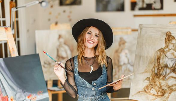 Malerin vor mehreren Leinwänden © proimagecontent, stock.adobe.com