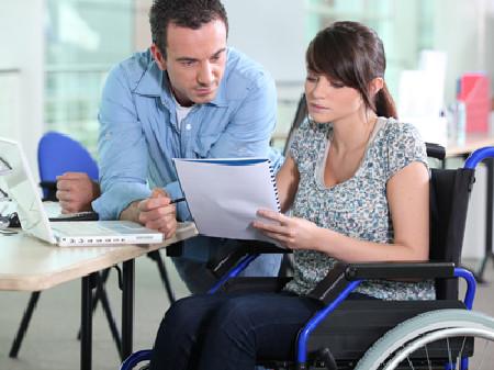 Junge Frau im Rollstuhl wird in ihrer Arbeit unterstützt © auremar, Fotolia