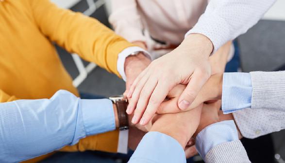 Menschen, die ihre Hände aufeinander legen © Robert Kneschke/stock.adobe.com