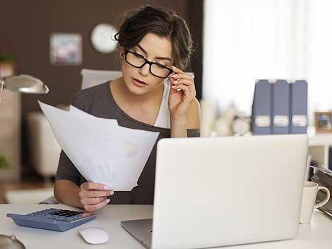 Frau mit Brille sitz vor Ihrem Laptop und prüft Unterlagen © Fotolia.com, gpointstudio