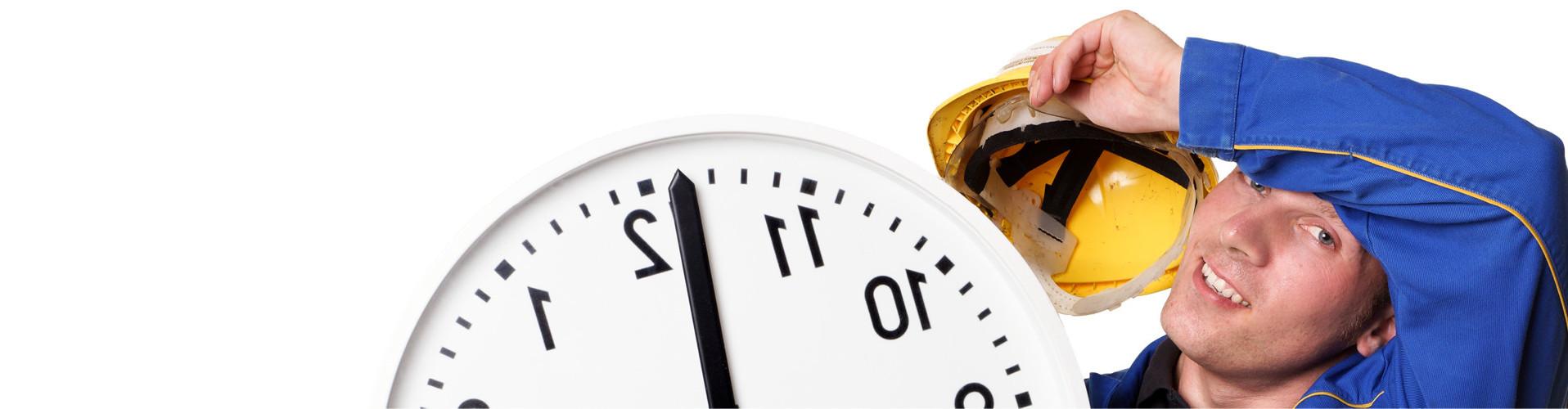 Mann mit Blaumann und Helm hält eine große Uhr © underdogstudios, stock.adobe.com