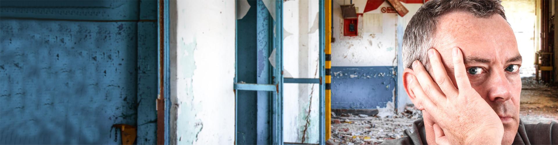 Ein Mann sitzt in einem heruntergekommenen Fabriksgebäude und blickt verzweifelt © Giuseppe Porzani, stock.adobe.com