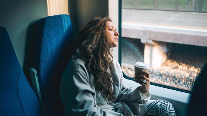 Junge Frau mit Coffee To Go in der Hand schaut nachdenklich aus dem Zugfenster © Gregory Lee, stock.adobe.com