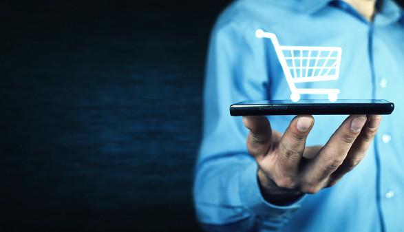 Mann hält Handy in der Hand mit Einkaufswagensymbol © andranik12/adobe.stock.com