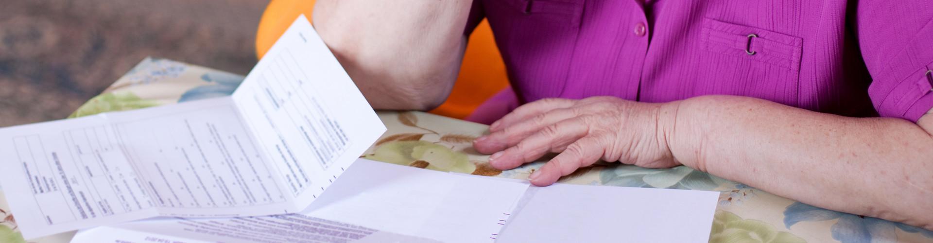 Man sieht die Hände einer älteren Frau, die über einen Tisch gebeugt ist, auf welchem eine Abrechnung liegt © M.Dörr & M.Frommherz, stock.adobe.com