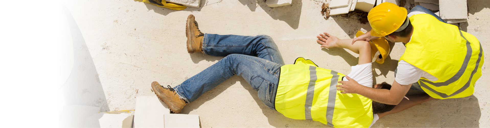Ein Arbeiter auf der Baustelle beugt sich über einen zweiten Arbeiter, der am Boden liegt © Halfpoint, stock.adobe.com
