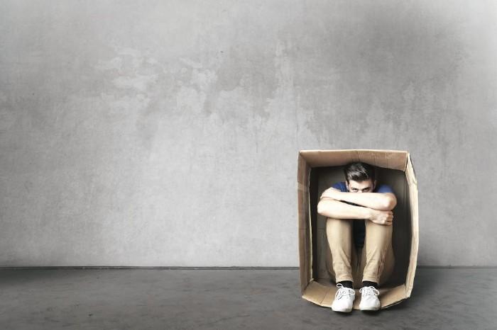 Junger Mann sitzt in Pappkarton © olly/stock.adobe.com
